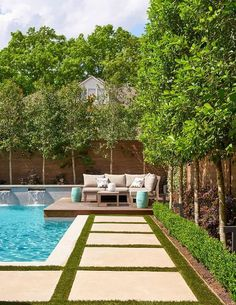 Along the edge of an in ground pool fitted with fountains, grass pavers lead to an beige sectional accented with beige pillows and flanked by turquoise blue drum stools.