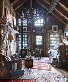 In the guesthouse of Birrittella's Sundance, Utah, property, the Navajo weavings are from the early 1900s, the cowhide-covered trunk is from the 1890s, and the chandelier and floor lamp are by Firesong Forge. - ELLEDecor.com