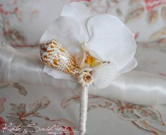 The White Orchid Seashell Boutonniere is an elegant and unique boutonniere for a beach, destination, or summer wedding. Each boutonniere is handmade