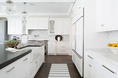 Amazing kitchen features Regina Andrew Large Globe Pendants illuminating a crisp white center island paired with black countertops framing a farmhouse sink and a gooseneck faucet facing an under cabinet fridge across from a white and gray striped runner atop dark floors.
