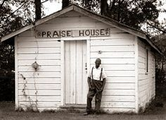 """A Gullah """"praise house,"""" a surviving example of slaves' secret meeting places, and its pastor, Rev. Henderson; St. Helena Island, South Carolina, circa 1995."""