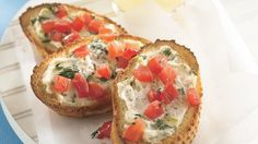 "Garlic Cream Cheese Crotini: 20 slices of 1/2"" thick French bread; 1 tablespoon olive; 1/2 cup Philadelphia garlic-and-herb cream cheese spread; 4 medium green onions, chopped (1/4 cup); chopped fresh plum or Roma tomatoes."