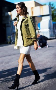 Alexa Chung wears a white knit mini dress with a military jacket, shoulder bag, and lace-up boots  @andwhatelse