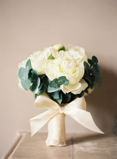 In keeping with the stylishly simple deco, Gina's bouquet was composed of white peonies, ivory Avalanche roses and eucalyptus leaves.Click here to see all the pictures form Gina and Tom's day