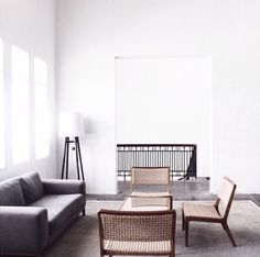 grey living area sofa white walls wicker chairs