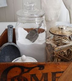 Vintage crate with glass canisters filled with laundry soap & wood clothespins.