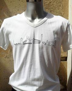T-shirt BORDEAUX Skyline© blanc - T-shirt en col V pour homme orné du logo BORDEAUX Skyline© sur le devant. Moderne et élégant, il apporte une touche urbaine à la silhouette. Un cadeau idéal pour toute occasion et un joli souvenir de Bordeaux.