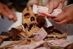 Bangkok, Thailand: Banknotes are placed on unclaimed human remains removed from graves, during a Thai Chinese ceremony at the Mang Teung Sua Jung cemetery