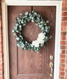 """DIY Eucalyptus wreath, 24"""" wreath, and 3 white hydrangeas from Hobby Lobby. Faux eucalyptus 8 pieces from Ikea. Arrange on the wreath and secure with Floral wire."""