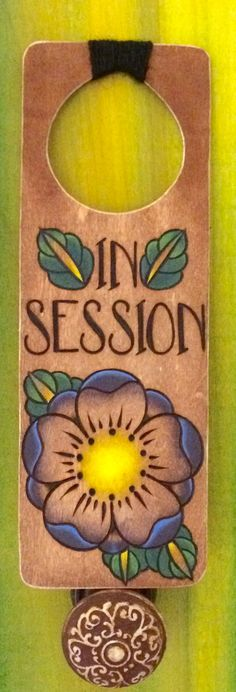 "Rustic wood-burned ""In Session"" door hanger with purple blossom flower artwork & black twine. https://www.etsy.com/shop/DesignsByHeidiLynne"