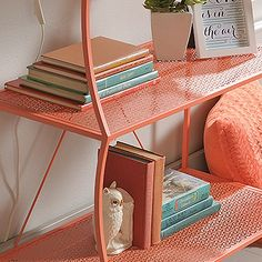 Tiered shelves feature geometric perforated pattern. Finished on all sides for versatile placement. Powdercoated metal construction. Coral.