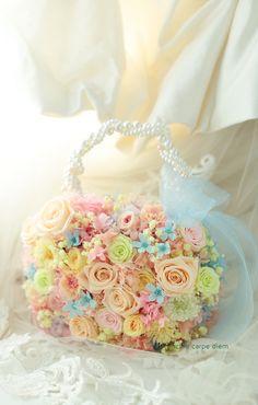 プリザーブドフラワーで作るバッグ型ブーケ、 結婚式のテーマはシンデレラ。 薄いブルーのドレスにあわせて水色のリボンと、 ブルースターをいれていま...