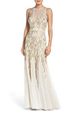 This airy mesh gown is detailed with floral beading that descends toward the twirly godet-flared skirt.