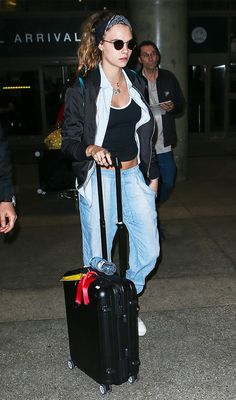 Cara Delevingne wears a black tank top, denim shirt, bomber jacket, round sunglasses, layered jewelry, and denim jogger pants