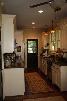 off white kitchen w/ black door, windows above sink