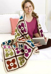 """RED HEART® """"Soft Yarn"""" is used in this free crochet afghan pattern. Make a floral motif afghan using the popcorn stitch. Make 35 floral motifs in four fun colors. This free crochet afghan pattern is great to make after winter as soon as the weather begins to warms up. Take this afghan to the park with you and relax with a good book."""