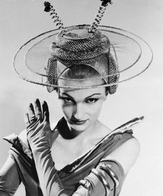 04 Apr 1956, Boston, Massachusetts, USA — Juli Dane modeling a futuristic hat, for brides a thousand years from now, at a Boston fashion show. It's from the famed Golden Wedding collection of bridal gowns and accessories of the past, present and future. The dual antennas and headset are supposed to let the young bride, honeymooning on the moon, keep in touch with family and friends on earth
