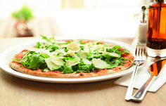 Our pizza is baked in the stone oven with only tomato sauce and mozzarella, and then topped with spicy rocket lettuce/arugula and Italian hard cheese.