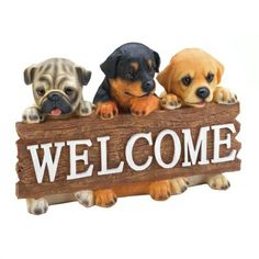 """Doggy Welcome Plaque  Welcome friends and family to your home with eternally cute puppy dog faces!  This charming wall plaque features three little pups holding a wood-style sign decorated with the word """"Welcome"""". Made from durable polyresin and features vibrant colors and details.  #CelestialDecor #Onlineshop #Dog #decorations #homerenovation #homeremedies #WallArt #Art #InterialDesign #Plaque #Welcome #puppies #office #studio #therapy #Clinic #DoggyDayCare"""
