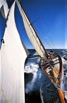 Classic sailboat with rail in the water