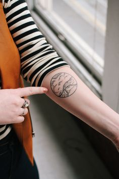 Tattoo of a landscape inside a circle on inside arm of female. Black and white line drawing. Road travel, ink, tat.