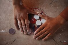 In this Wednesday, July 2015 photo, a boy arranges disks for a game of carrom during break time at a school in Kathmandu, Nepal.