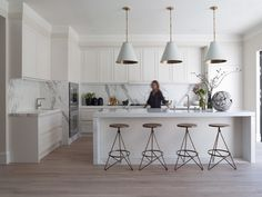 """Marble rules in this modern kitchen — Calacatta Oro runs along the counters and up the backsplash; the island is Thassos. The """"whitewashed"""" floor (stained with Rubio Monocoat) picks up the gray striations in the stone. There is a quartet of three-legged swivel stools (available from Arteriors) at the island, and oversize pendants from Visual Comfort."""