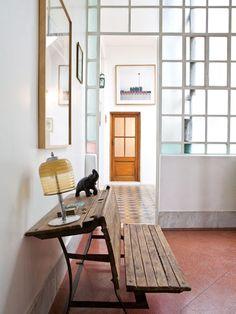 Hall de entrada minimalista con banco tipo escuela, lámpara y cuadro en un ph reciclado.