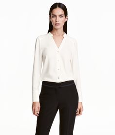 Natural white. V-neck blouse in slightly thicker, crêped fabric with a small stand-up collar, snap fasteners at front, and long puff sleeves with wide cuffs
