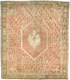 A late 19th century antique Ghiordes (Giordes) rustic carpet the faded pinkish brown field with floral sprays around a central medallion