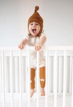 Adorable happy baby jumping in her crib wearing stylist hipster baby monochrome knit outfit. Warm and cozy and perfect for playtime, organic footless gold mustard leggings with little illustrated happy faces detail on the knees. from Noble Carriage's Hansel From Basel collection.
