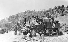 A company M3 half-tracks armed with 75 mm cannons. provides fire support in Sicily in the summer of 1943.