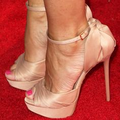 Sofia wears a pair of satin platform sandals with a knot detail at the back