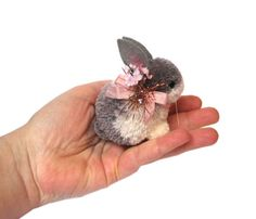 This cutest scene features one lovely handmade woolen pom pom Baby bunny. The adorable bunny wears a beautiful silk pink ribbon around her neck with flowers and pink tinsel to add sparkle. She has beautiful glass black eyes and a cute pom pom tail. A very unique and special one of a