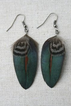 These earrings are handmade using Spruce Grouse grey and black stripy feathers and blue shimmering magpie feathers using black gunmetal findings .
