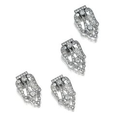 FOUR DIAMOND CLIPS,  CIRCA 1930.  Each open work clip of shield design, set with circular- and single-cut diamonds; together with a later hinged bangle, the terminals can be fitted with two of the clips, bangle unillustrated,   circumference approximately 165mm.