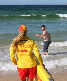 The Los Angeles Dodgers' Drew Butera, right, heads into the water while surf lifesaver Sophie Thomson follows with a rescue board at Bondi Beach in Sydney, Wednesday, March 19, 2014. The Major League Baseball season-opening two-game series between the Los Angeles Dodgers and Arizona Diamondbacks in Sydney will be played this weekend. (AP Photo/Rick Rycroft)
