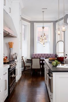 Gray walls highlight the beautiful white crown molding and trim, which maintain the original character of this home. Modern upgrades give the kitchen a fresh look without compromising its integrity. A purple settee in the breakfast nook brings a sophisticated pop of color.
