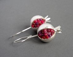 Lovely, sensuous pomegranate earrings with strong metaphorical allusions. These sculptural pomegranates are 3-dimensional hollow forms; hand constructed -- raised, soldered and surface finished -- with matte brushed silver, ruby, purple amethyst, rhodolite garnet, carnelian and red/pink garnet beads.  These one of a kind earrings measure approximately 45 mm high from top of the ear wire to bottom of the crown X 17-18 mm wide X 18 mm deep.  the calyx - the little crown - can be made with…