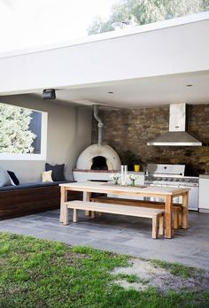 A wooden table and bench seats, paired with built-in outdoor seating arrangements and a wood fired pizza oven are ideal for entertaining in this contemporary family situated in Melbourne. *Photography by James Henry* Outdoor Kitchen Patio, Pizza Oven Outdoor, Outdoor Kitchen Design, Outdoor Rooms, Outdoor Living, Outdoor Furniture Sets, Outdoor Decor, Outdoor Chairs, Wooden Outdoor Table