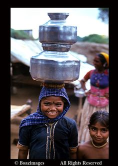 A girl with water vessels on her head.  Gujarat,India.