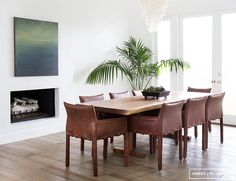 Earthy and bright dining space with leather dining chairs, small fireplace, and indoor plant