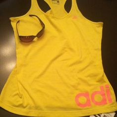 """Adidas Yellow Performance Linear Tank Top Authentic Adidas Performance Yellow Linear Tank Top. Racerback. Tunic Length. Neon Orange Accents including Large """"adi"""" on the Front Left Bottom & """"das"""" on the Back Left Bottom. Climalite: Stay Dry. Stay Comfortable. Draws Sweat Away from your Skin. 70% Cotton/30% Polyester. Brand New. Excellent Condition. No Trades. Adidas Visors are also Listed in my Closet including this White one that coordinates perfectly with this top.  See Same Top in Pink…"""