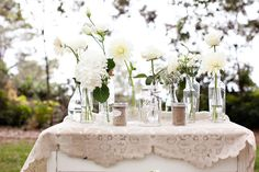 single stems could look so beautiful in simple glass jars of various types and sizes surrounding lanterns