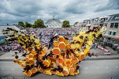 Tens of bees swarm around this (sadly inedible) orange and yellow honeycomb as…