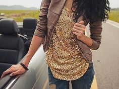 motorcycle jacket with repeating pattern cloth on a ruched blouse and torn jeans.