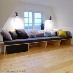 Die gemütliche Sitzbank am Fenster lädt zum Entspannen ein. Sie geht über die gesamte Fensterfront, bietet Stauraum und Platz für viele. In der Kombination aus Multiplex natur und Multiplex schwarz wirkt sie leicht und modern und fügt sich mit individuellen, farbigen Auflagen und Kissen in den Wohnraum ein.