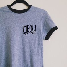 "Our super soft ringer tee, featuring contrasting black neckline and sleeve bands, with our ""Meow"" graphic on the left chest. Our ringer tees are a staple to any girl's closet, adding a touch of grunge. They look great styled casually with jeans and boots, or dressed up with a cute plaid skirt. More sizing and composition info here."