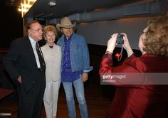 Musician/actor Dwight Yoakam (R) poses with his mother Ruth Ann and bluegrass music legend Earl Scruggs, whose wife Louise takes a picture after a ceremony honoring Yoakam with a star on the Hollywood Walk of Fame June 5, 2003 in Hollywood, California.
