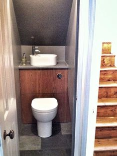 A tiny toilet and sink in one unit for under the stairs.